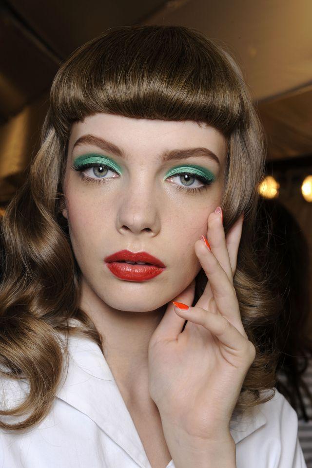 """Styl retro króluje w modzie, a także makijażu. W tym przypadku oko zostało podkreślone zielonym cieniem. Na powiece namalowani także grubą czarną kreskę tuż przy linii rzęs. Dolną powiekę zostawiamy """"czystą"""" (można jedynie użyć tuszu do rzęs). Usta wyraziste, w kolorze czerwieni lub soczystego różu. Taki makijaż promowała ostatnio marka Dior"""